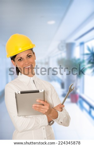 Woman engineer with the tablet and wrench in hands