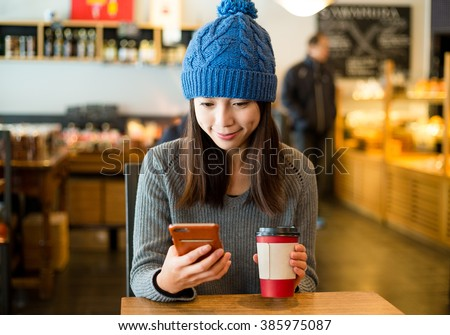 Woman enjoy her coffee and look at mobile phone