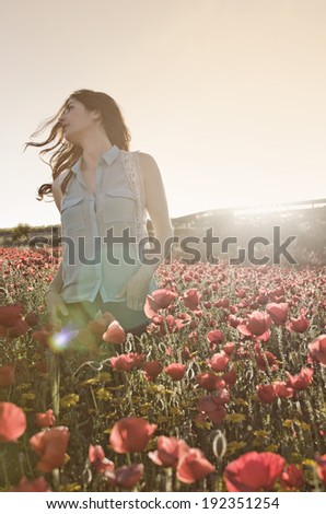 Woman enjoy her freedom in the poppies flowers - stock photo