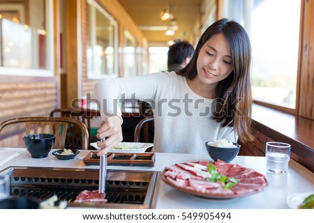 Woman enjoy roasted beef in japanese restaurant