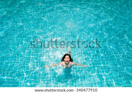 Woman enjoy swimming on a blue water pool with happy smiling expression face.  - stock photo