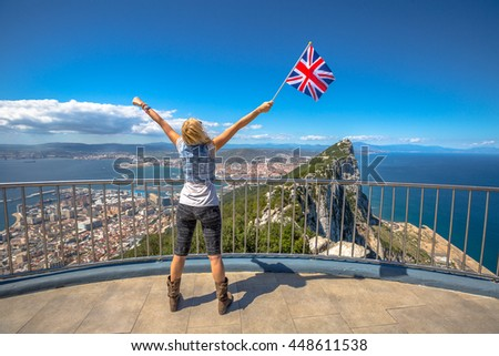 Woman enjoy with the British flag in hand on top of Gibraltar Rock. Gibraltar is a territory of South West Europe Which is part of the United Kingdom. - stock photo
