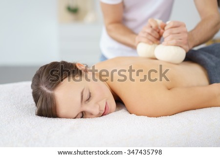 woman enjoying a beauty treatment with herbal compresses in a spa with eyes closed - stock photo
