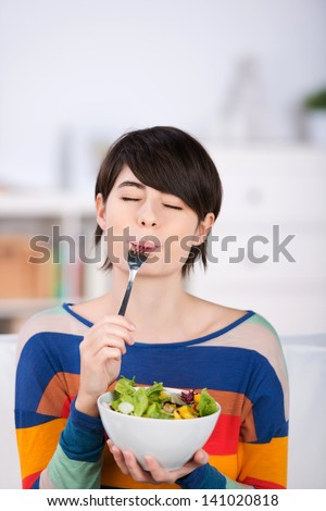 Woman enjoying a bowl of fresh leafy green salad salad standing with her eyes closed in pleasure and a fork in her mouth - stock photo