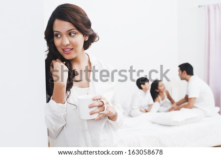 Woman enjoying a cup of coffee with her family in the background - stock photo