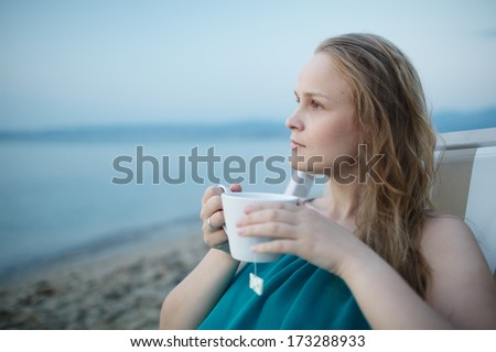 Woman enjoying a cup of tea at the seaside sitting relaxing on a deckchair with a blissful expression overlooking a tropical beach