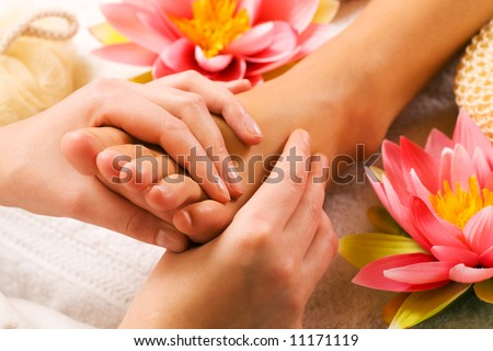 Woman enjoying a feet massage in a spa setting (close up on feet) - stock photo