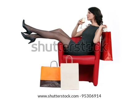 Woman enjoying a glass of wine during a shopping trip - stock photo