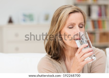 Woman enjoying a healthy glass of fresh water sipping the liquid with her eyes close in bliss and a look of pleasure - stock photo