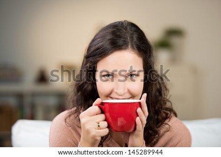 Woman enjoying a large cup of freshly brewed hot tea as she relaxes on a sofa in the living room - stock photo