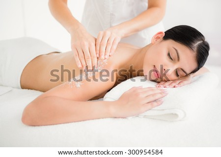 Woman enjoying a salt scrub massage at the health spa - stock photo