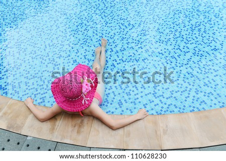 woman enjoying a swimming pool in a large sunhat - stock photo