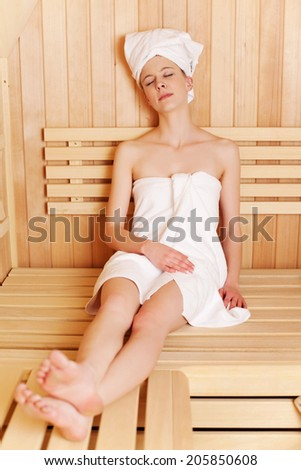 Woman enjoying a traditional sauna sitting stretched out on a wooden bench wrapped in fresh white towels with her eyes closed - stock photo