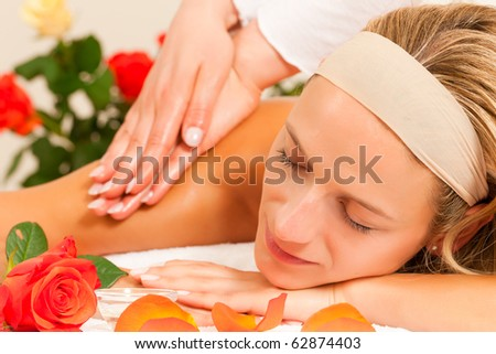 Woman enjoying a wellness back massage in a spa setting with roses in the background, she is very relaxed (close-up) - stock photo