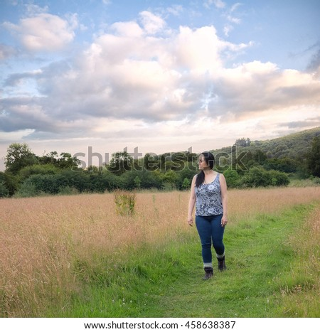 Woman enjoying an evening stroll through barley field in summer.