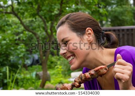 woman enjoying barbecue outdoors - stock photo
