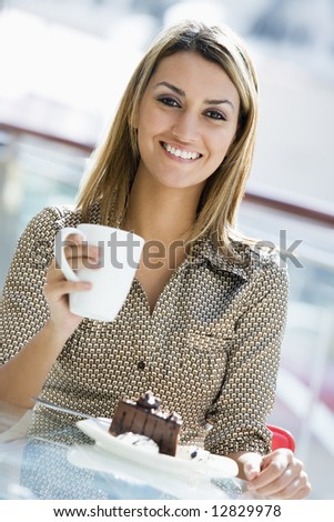 Woman enjoying cup of coffee and piece of cake at cafe