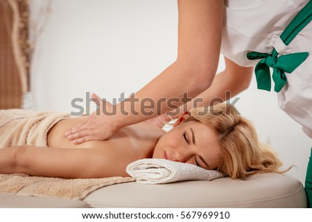 Woman enjoying during a back massage at the spa.