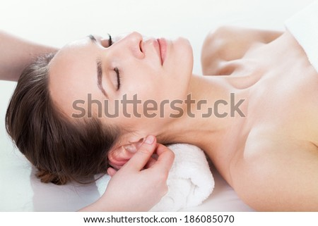 Woman enjoying ear massage at beauty salon