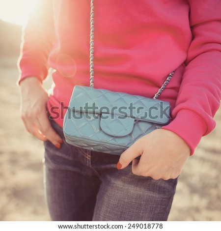 Woman enjoying freedom and life on beautiful and magical sunset. relaxed and happy. Fashion handbag. Photo with instagram style filters - stock photo
