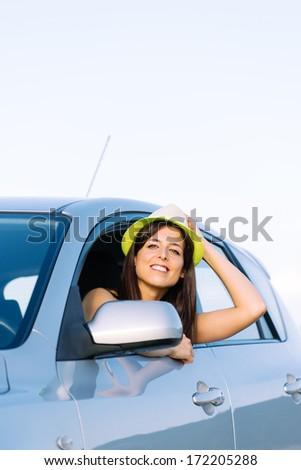 Woman enjoying freedom on car roadtrip. Happy girl having fun on travel. - stock photo