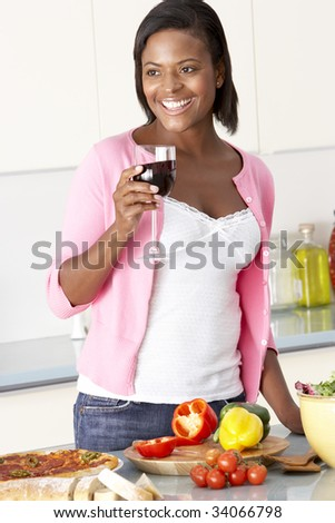 Woman Enjoying Glass Of Wine In Kitchen - stock photo