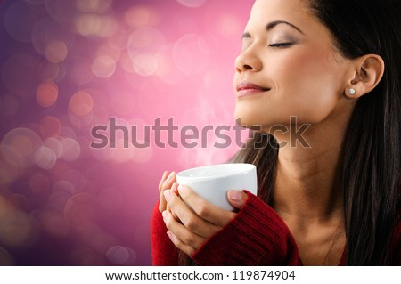 woman enjoying hot steaming cup of coffee with bokeh lights and beautiful portrait - stock photo