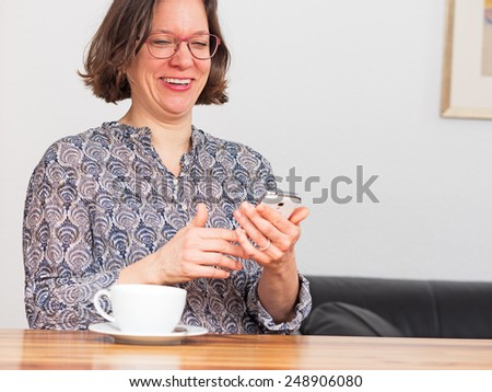 Woman enjoying message on her mobile phone - stock photo