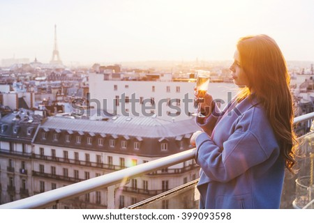 woman enjoying panoramic view of Paris and Eiffel tower at sunset, holding glass of wine or champagne in rooftop luxury restaurant - stock photo