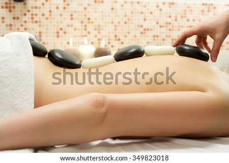 Woman enjoying stone therapy/A female receiving massage and hot rock treatment to back and neck at a beauty salon or day spa facility/Woman Enjoying Stone Therapy/  - stock photo