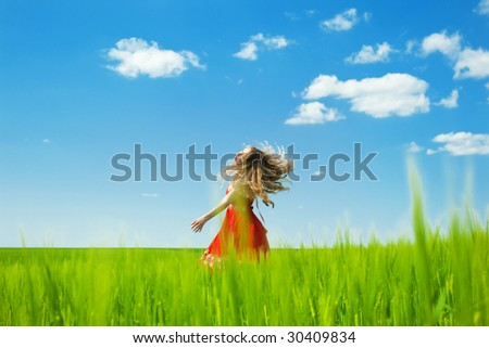 woman enjoying summertime and dancing in the field - stock photo