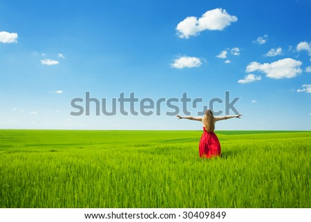 woman enjoying summertime;woman with open arms in green field - stock photo