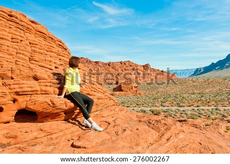 Woman enjoying view of red  rock formations in Valley of Fire State park, Nevada, USA
