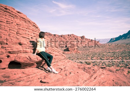 Woman enjoying view of red  rock formations in Valley of Fire State park, Nevada, USA. retro - vintage filter - stock photo