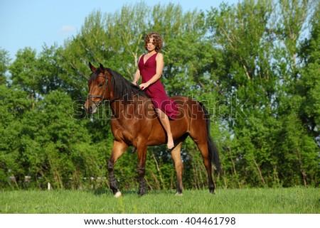 Woman enjoying while horseback riding  - stock photo