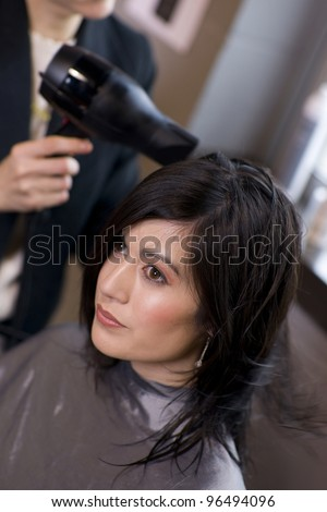 Woman Enjoys A Professional haircut style and blow dry at the salon