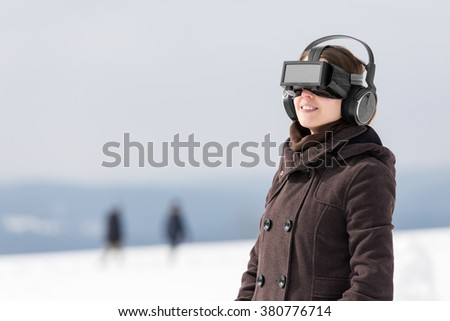 woman enjoys her virtual reality glasses in a winter landscape