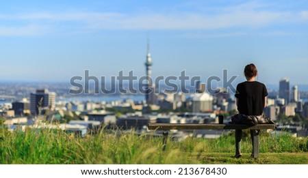 Woman enjoys spectacular morning views of Auckland city - stock photo
