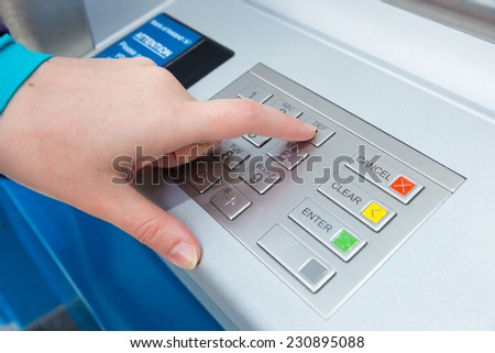 Woman entering her PIN at an ATM - stock photo