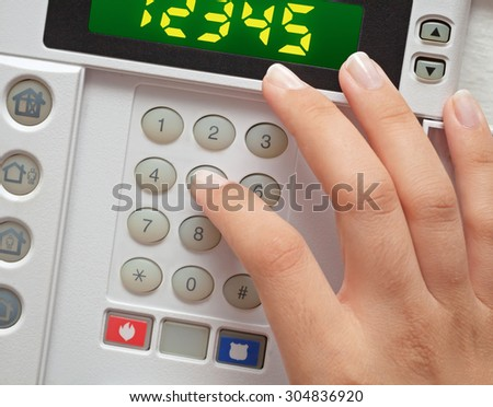 woman entering security code to alarm system - stock photo