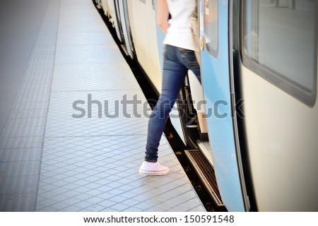 Woman enters train - stock photo