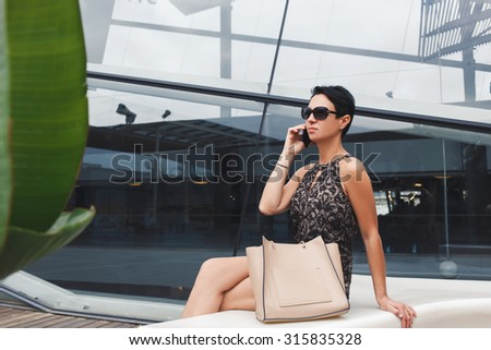 Woman entrepreneur discussing business ideas by her smart phone while sitting against office building, female employed dressed in elegant clothes having telephone conversation in urban setting - stock photo