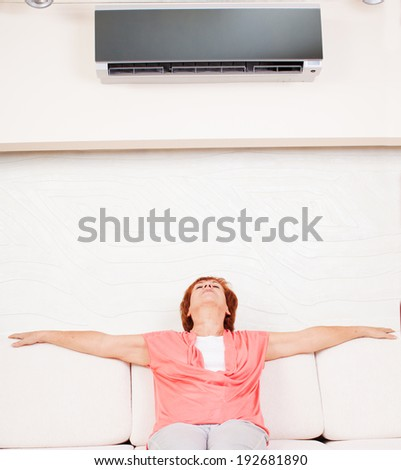 Woman escapes from the heat under the air conditioner at home. Happy mature woman on sofa - stock photo