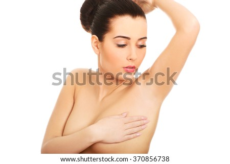 Woman examining breast.