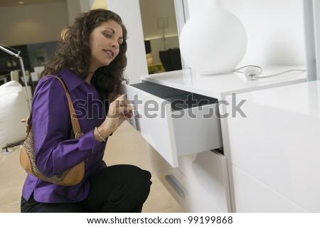 Woman Examining White Dresser - stock photo