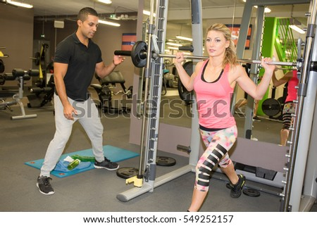 Woman exercise on shoulder press machine with personal trainer