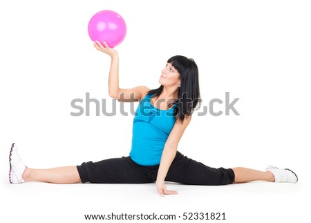 Woman exercise with ball doing splits on white background