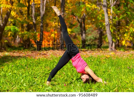 Woman exercises in the autumn forest yoga Adho mukha eka pada shvanasana pose - stock photo