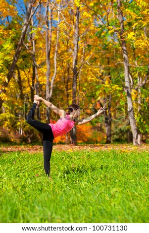 Woman exercises in the autumn forest yoga nataradzhasana pose - stock photo
