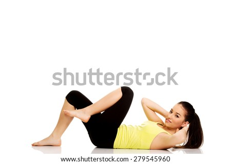 Woman exercising and doing a crunch to work her abs. - stock photo